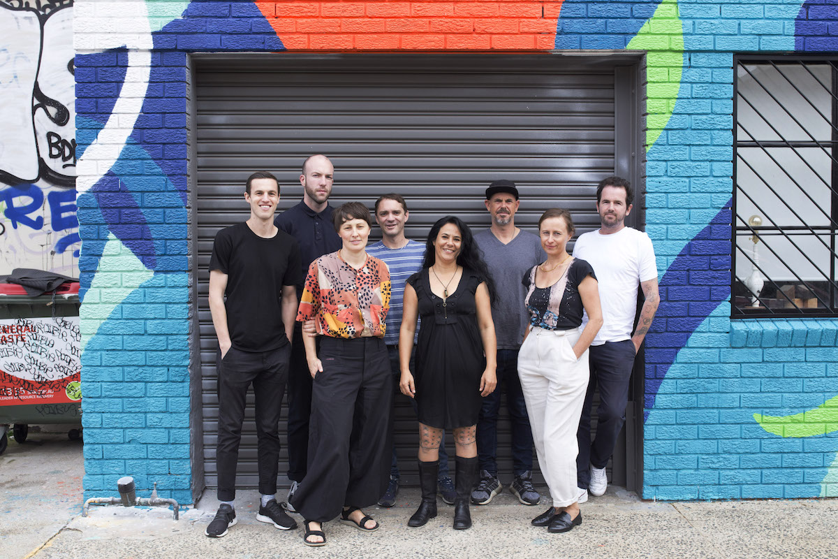 Group portrait for Shirlow Street Studios. Fom left: Mason Kimber, William Cooke, Izabela Pluta, Tim Silver, Stevie Fieldsend, David Griggs, Cybele Cox, and Phil James. Photo: Alexander Cooke. Courtesy of Shirlow Street Studios.