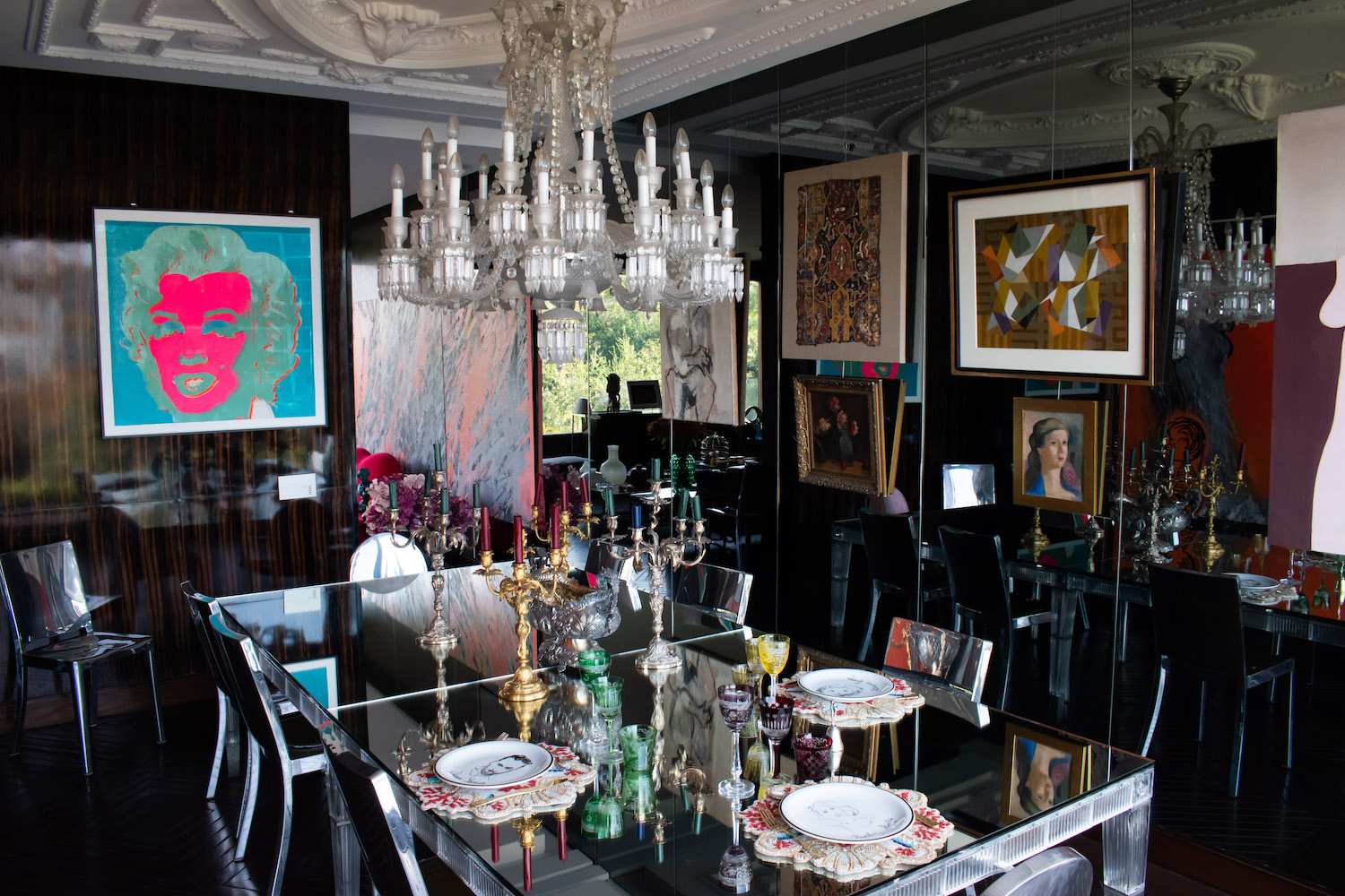 """Andy Warhol, """"Marilyn (F&S 30)""""; Grace Weinrib, """"Pencil (triptych) (partially seen in the back room); Enrique Castro Cid, """"Untitled""""; and Josefina Guilisasti, """"Fragmento Persa S XVII""""; Matilde Pérez, """"Flores"""" and """"Untitled""""; Graciela Aranis, """"Untitled""""; Roser Bru, """"Los Tiempos Han Cambiado"""" (partially seen on right side of image); Philippe Starck Emeco Hudson Chairs; Baccarat dinning table by Philippe Stark; and Baccarat chandelier Philippe Starck. Photo: Andrés Herrera. Courtesy of Juan Yarur."""