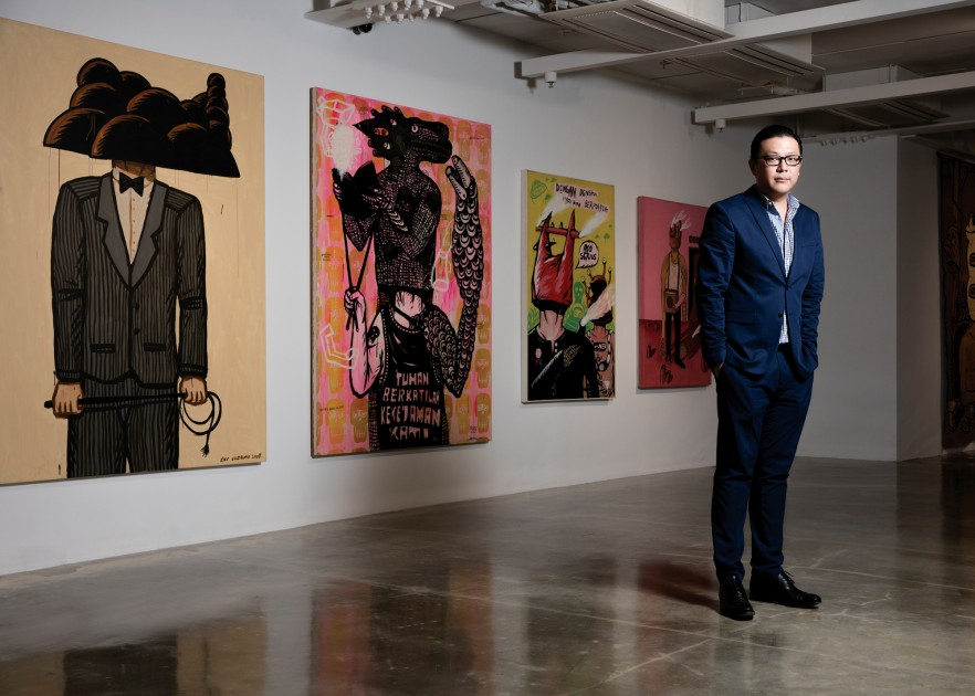 Tom Tandio standing in front of works by Eko Nugroho. Courtesy of Tom Tandio.