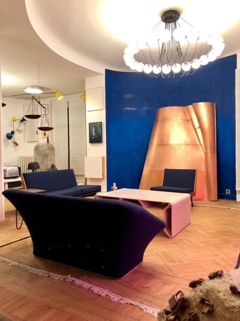 Copper sculpture by Danh Vo, Blue Wall and Carpet Border by Latifa Echakhch, alongside design pieces: « Cellae » Coffee Table by François Bauchet, sofa by Pierre Paulin, chandelier by Gino Sarfatti - Vintage Piece. Courtesy of Clémence and Didier Krzentowski.