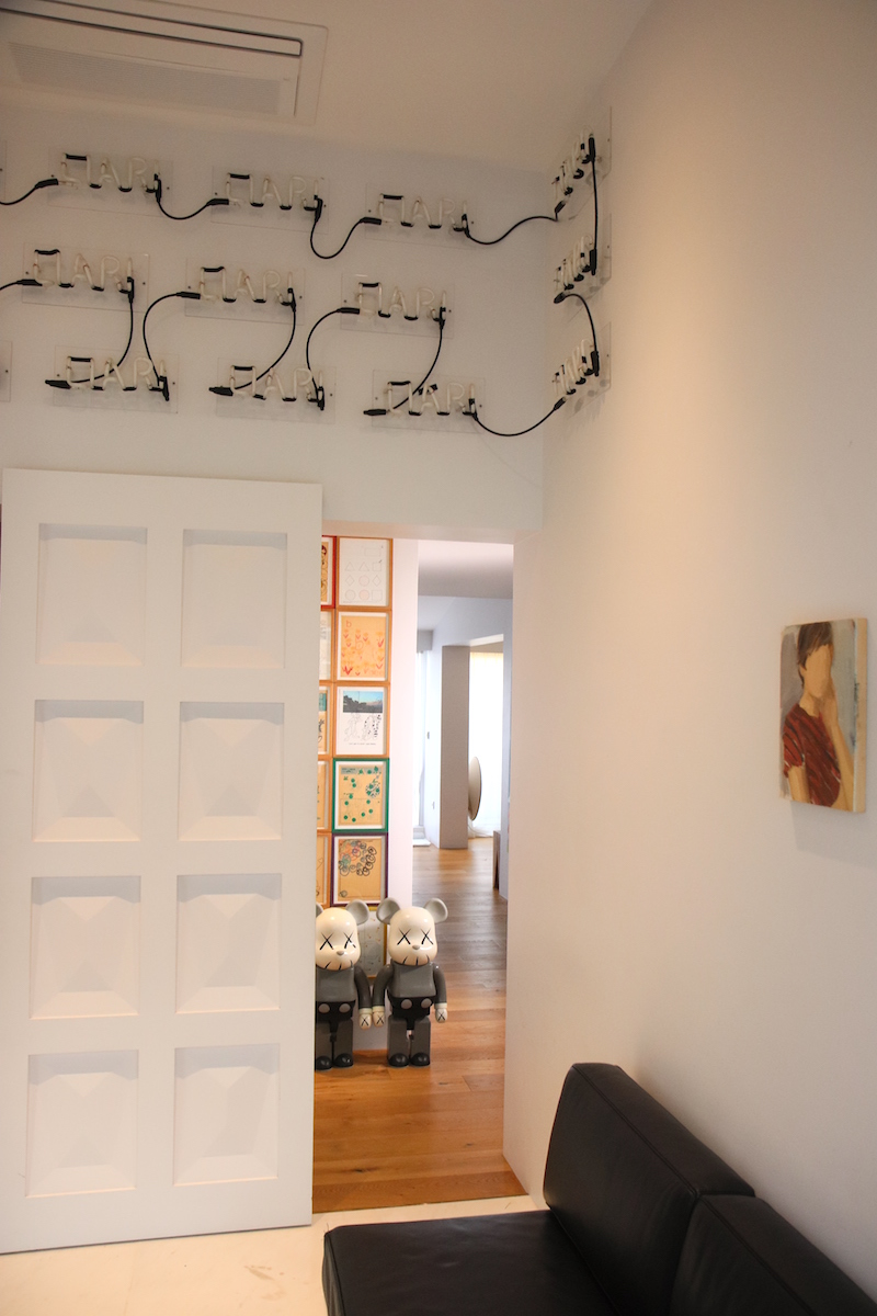 An artwork by Kiri Dalena above the door, and a portrait painting by Gideon Rubin on the right. Courtesy of Hee Jae Kang.
