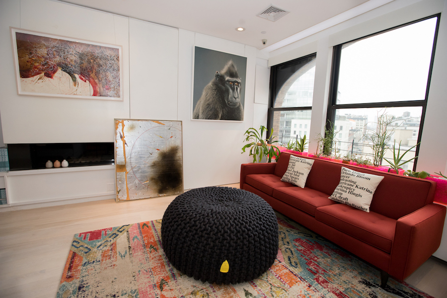 """The living room filled by pieces by Jose Parla, Name and Note, 2009; Davide Zucco, Untitled, 2014; Jill Greenberg, Anxious, 2007; Christian Meindertsma, """"Flocks Pouf""""; Elode Blanchard, Google News Top Searches in 2005 & Google News Top Searches in 2006. Courtesy of Sara and Marc Schiller."""