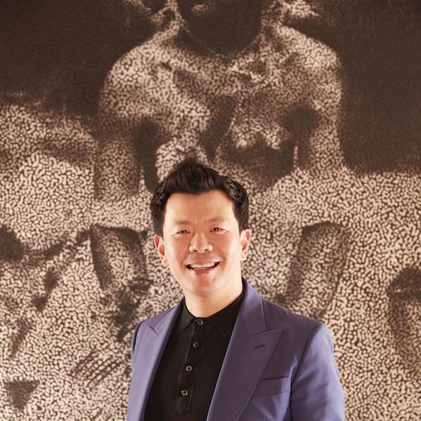 Dr. Terry Wu in front of art by Daniel Boyd. Photo: Zan Wimberley. Courtesy of Roslyn Oxley9 Gallery.