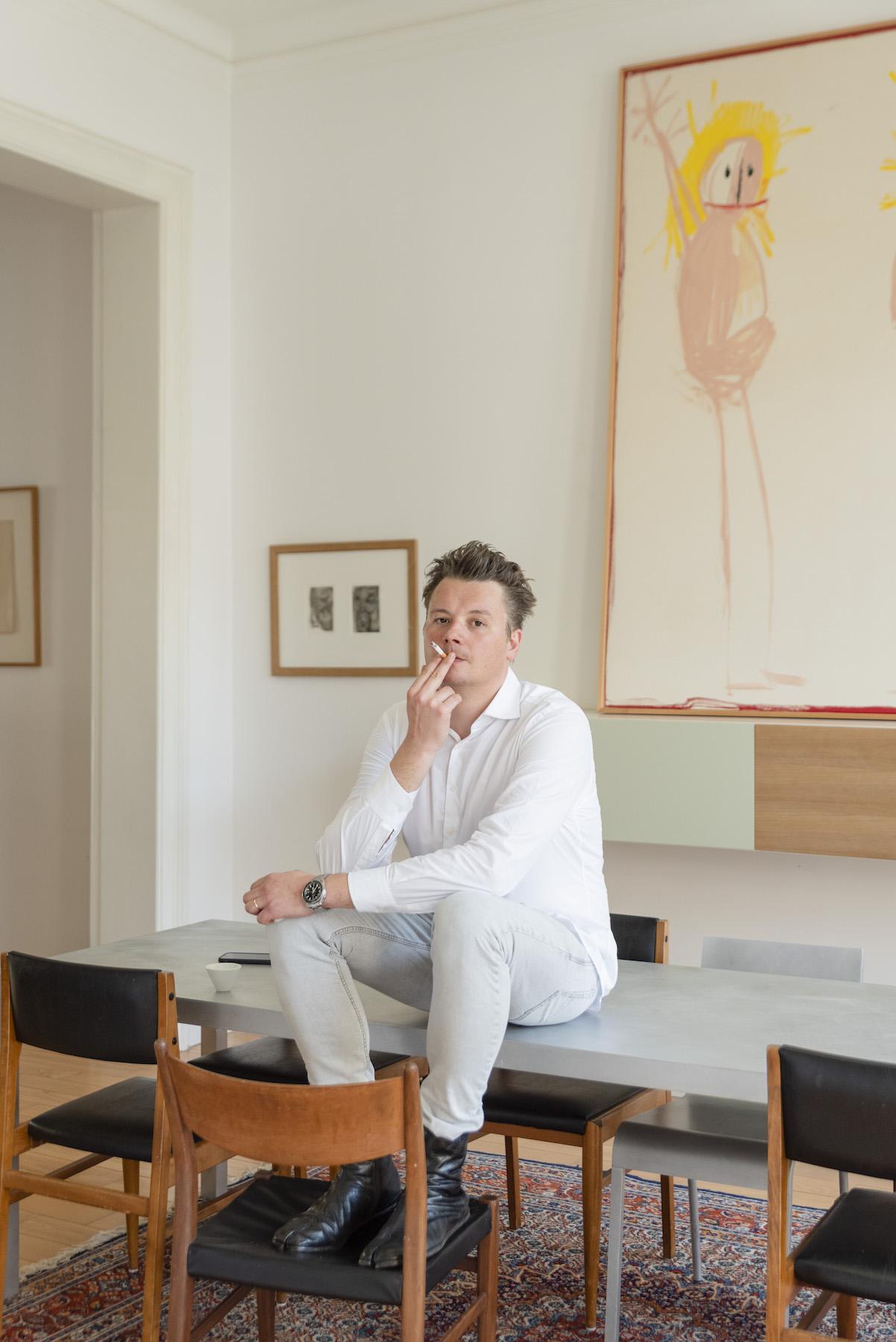 Joris Beernaert sitting in front of a work by Andi Fischer. Photo: Alexandra Bertels. Courtesy of Joris Beernaert.