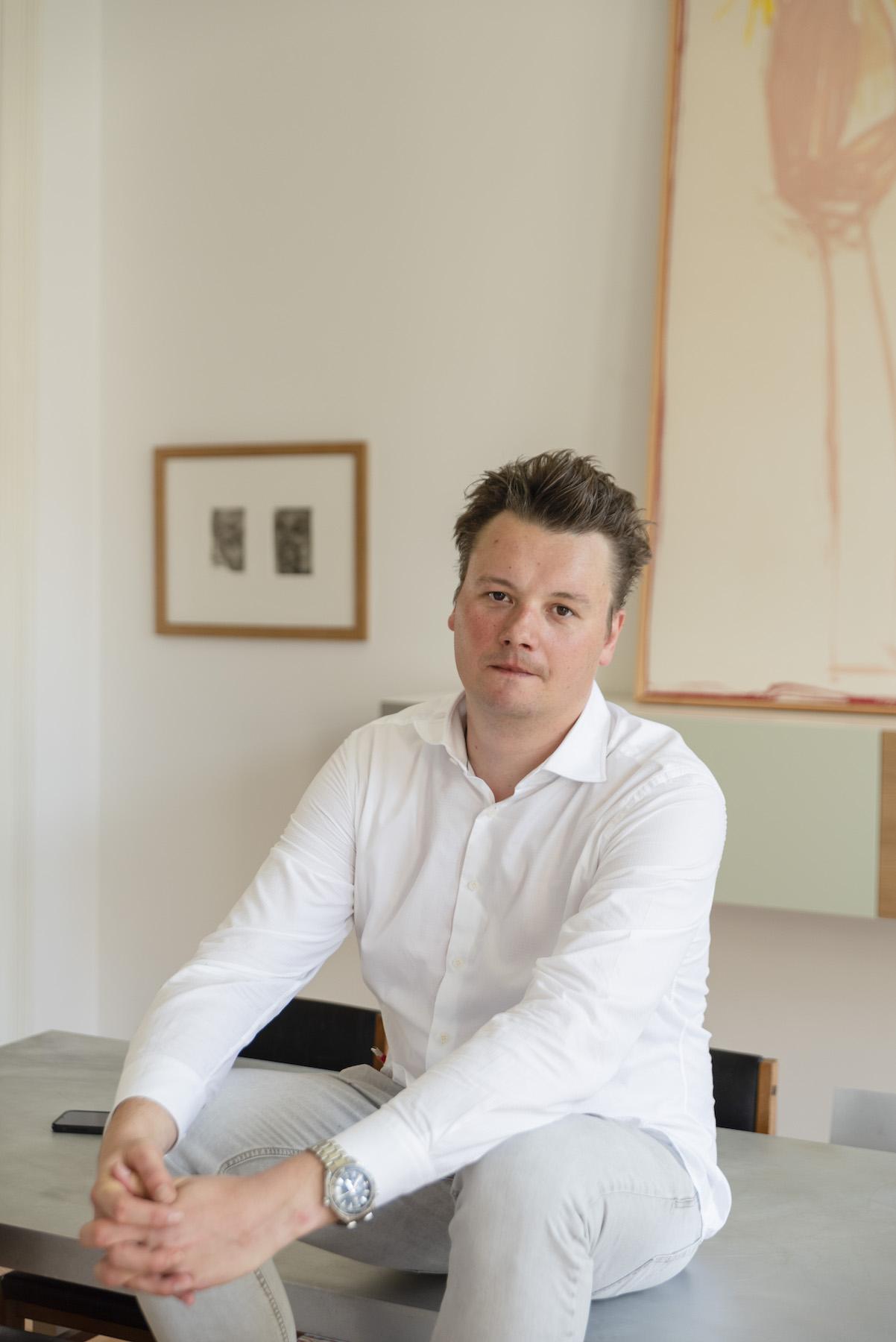 Joris Beernaert sitting in front of work by Fabrice Samyn. Photo: Alexandra Bertels. Courtesy of Joris Beernaert.