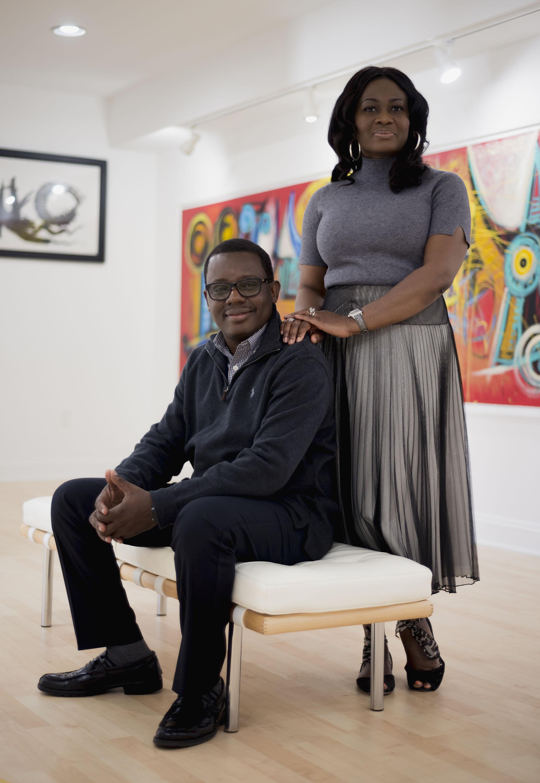 "Olusanya and Yinka Ojikutu with his large scale painting titled ""Remireke Festival"" (2016) in the background. Photo: Emma Howells. Courtesy of Olusanya Ojikutu."