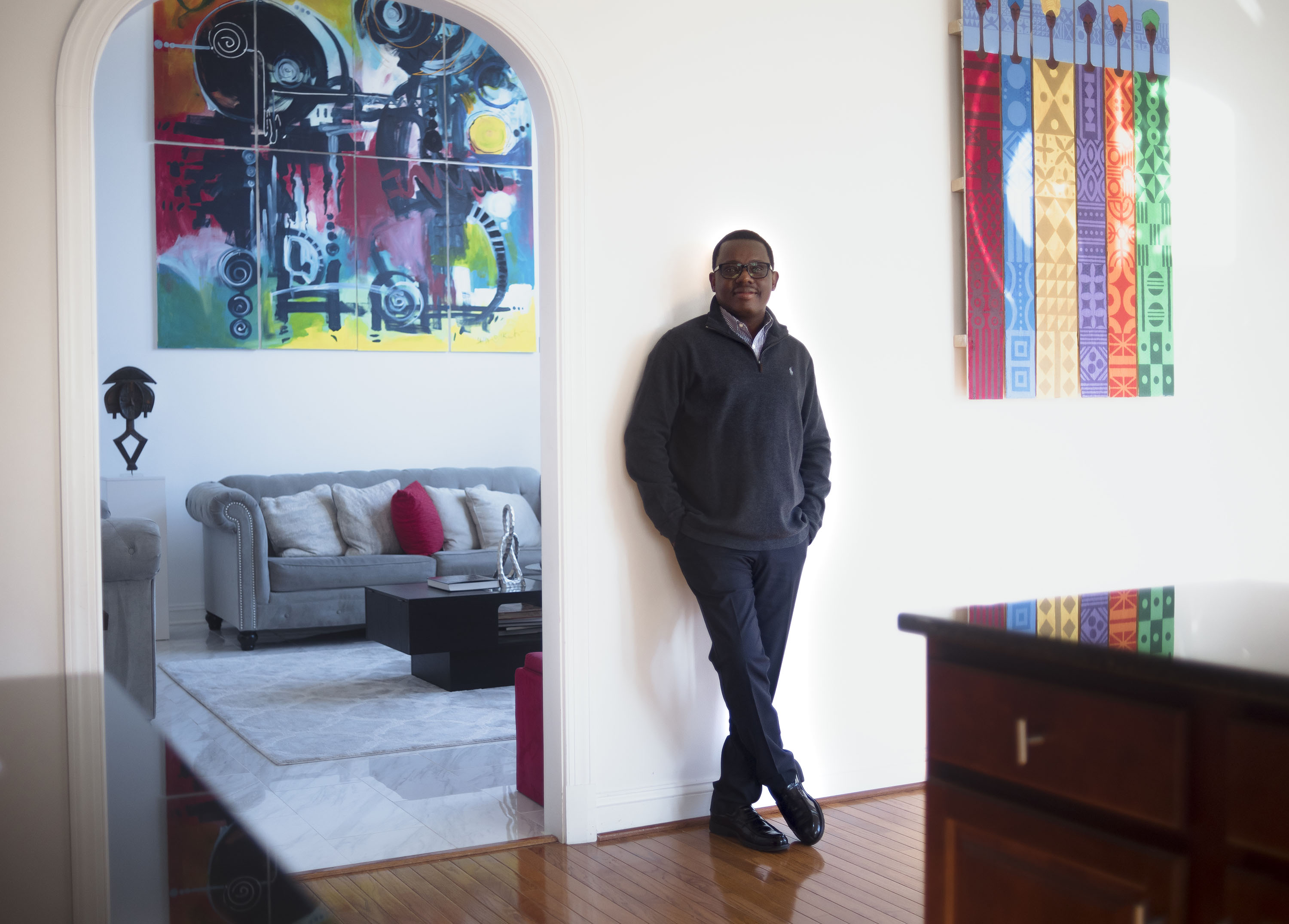 """Olusanya Ojikutu with, left, a Kota Reliquary Guardian Figure, center, detail of one of his own paintings, """"Labyrinth of Imagination"""" (2015), and right, a painting on a wood pallet by Dapo Ojoade. Photo: Emma Howells. Courtesy of Olusanya Ojikutu."""