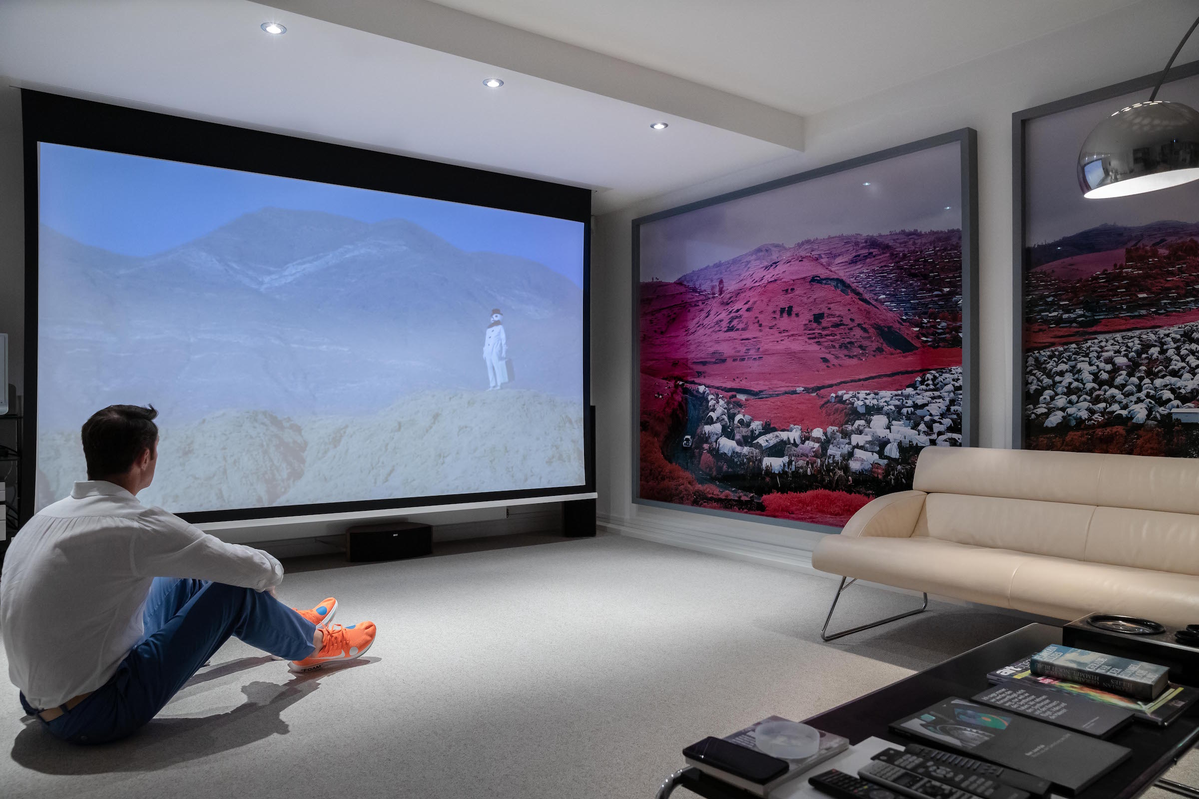 Mario sitting next to video screen, which is playing video of Friedrich Kunath, Untitled, 2009. Photos on the right by Richard Mosse, Thousends are Sailing I and II, 2012. Photo: Jens Braune del Angel. Courtesy of Collection von Kelterborn.