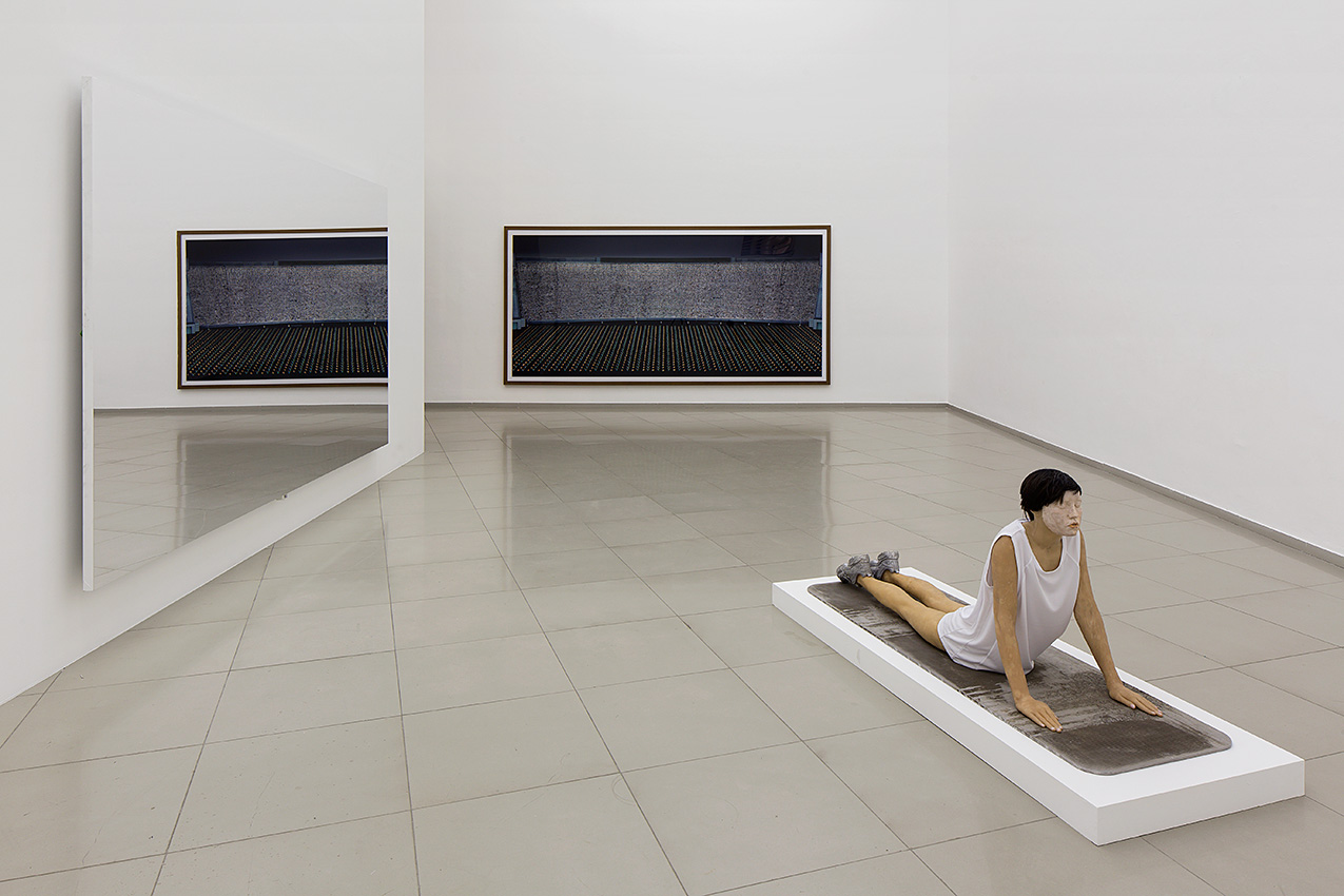 "Installation view from the exhibition ""Melting Walls"", Tel Aviv, 2015. On the floor: Andro Wekua, Should be Titled, 2011. On the left: Jeppe Hein, Mirror Wall, 2009. On the Back: Andreas Gursky, Pyongyang III, 2007. Courtesy of Igal Ahouvi Art Collection."