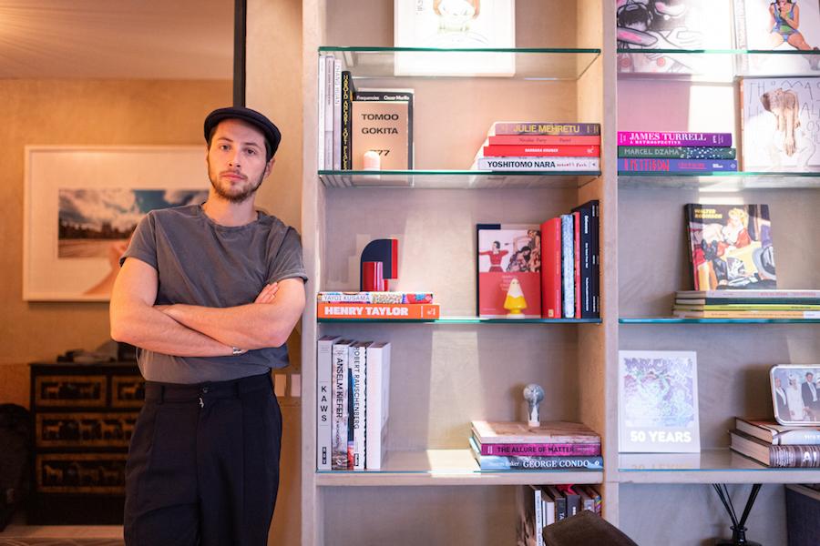 Oleg next to a shelf of art books and artworks. Courtesy of Oleg Guerrand.