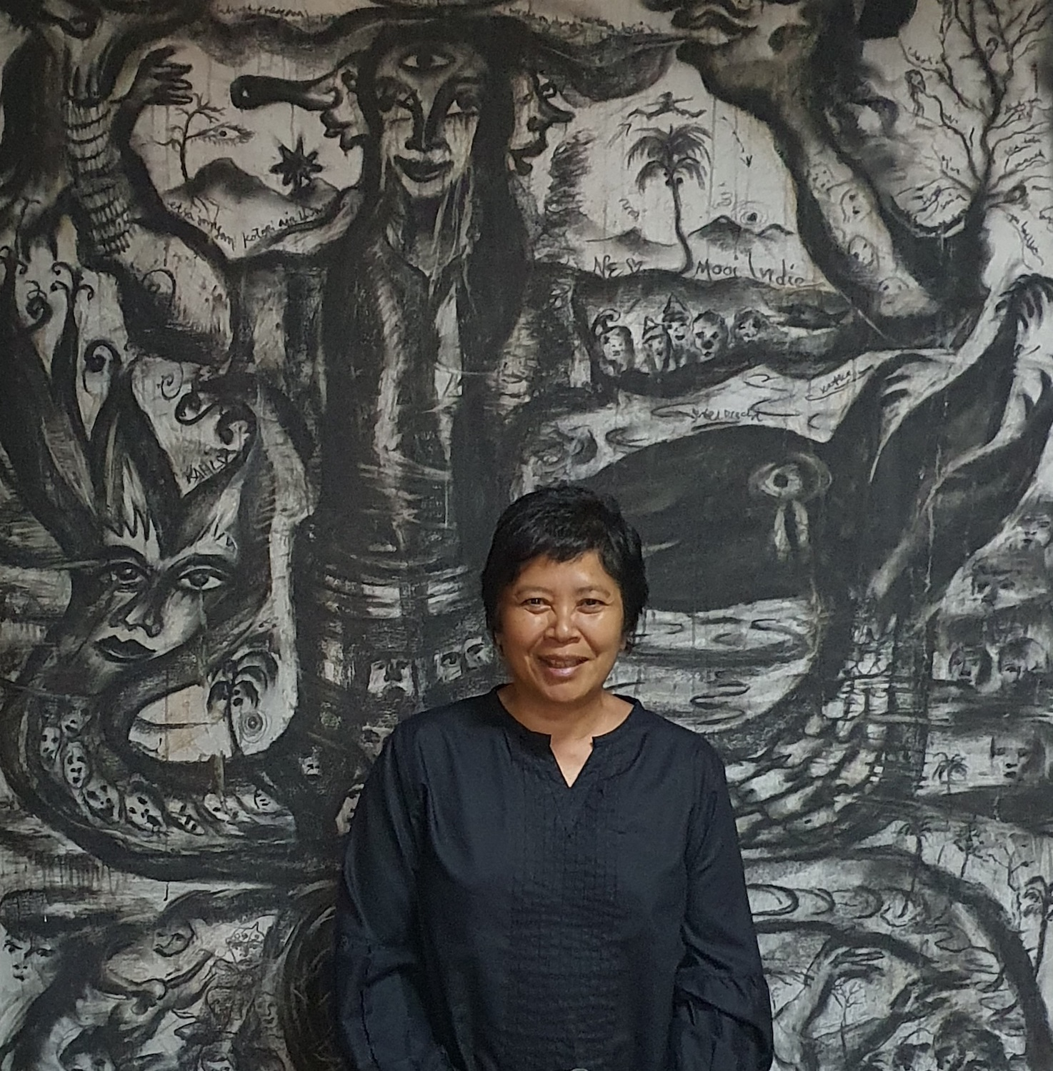 Andonowati at home with a work by Tisna Sanjaya in the background. Courtesy of Andonowati.